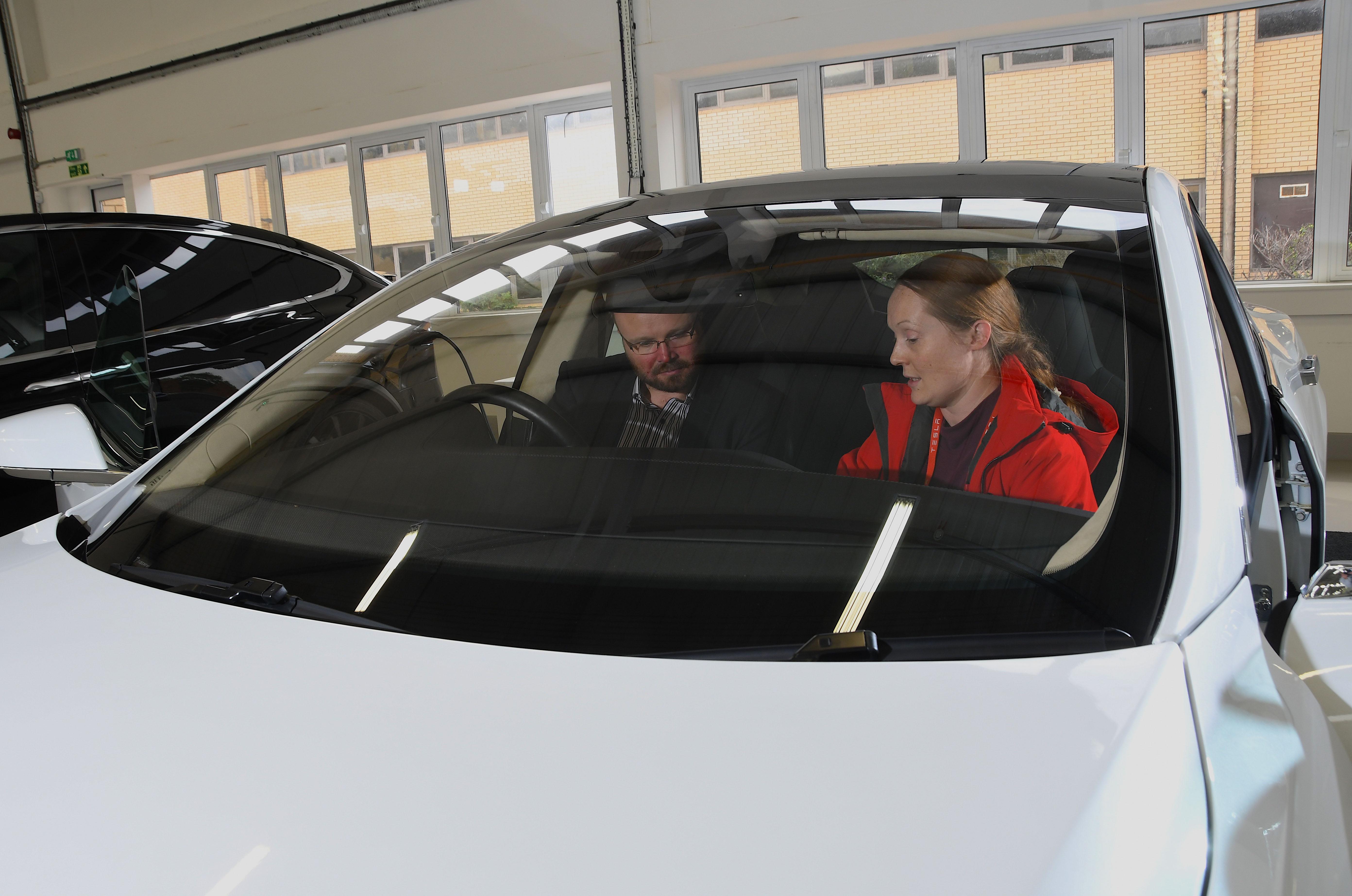Laura Hardy shows Alex Robbins around his Tesla long-temer